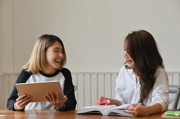 Fêmea junto usando tablet falando com educação.