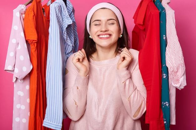 Fêmea linda alegre positiva com os olhos fechados em boutiqe. muitos cabides com roupas. a senhora sorridente encontra o que precisa. mulher com sorriso parece feliz. morena contente entre vestidos no shopping.