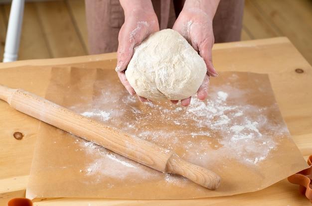 Fêmea mãos desenrolando a massa com um rolo
