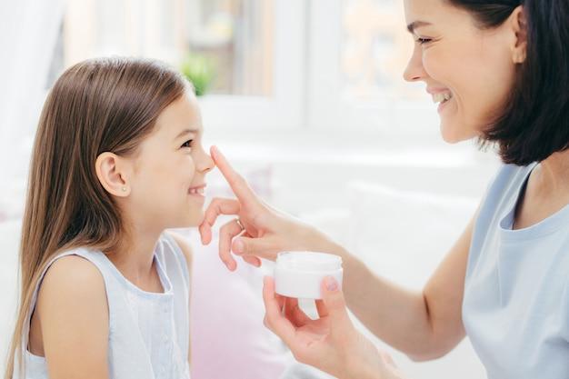 Fêmea muito alegre recebe procedimento de beleza da mãe carinhosa. mulher jovem e atraente aplica creme de beleza no nariz da filha
