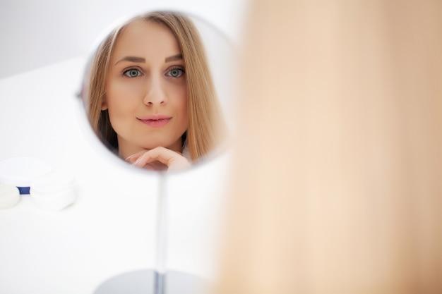 Fêmea muito jovem, olhando no espelho depois do banho
