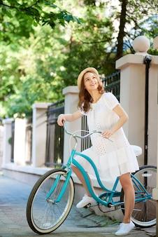 Fêmea muito jovem parou para admirar enquanto andava de bicicleta azul pela bela rua com cerca de pedra e árvores verdes