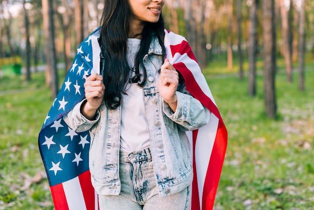 Fêmea na jaqueta jeans com bandeira dos eua