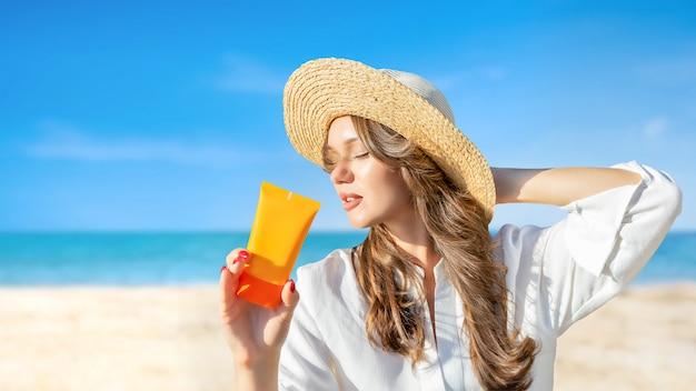 Fêmea no chapéu de palha praia segurando protetor solar spf creme no pano de fundo ensolarado rochoso. proteção contra raios uv do sol, férias de verão. etnia européia.