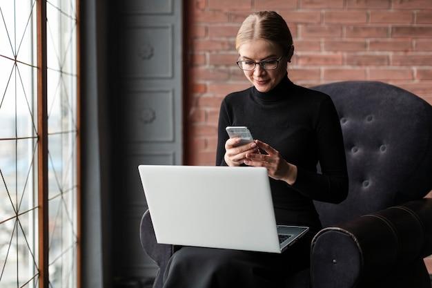 Fêmea no sofá com o laptop e celular