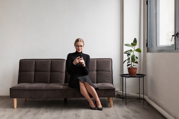 Fêmea no sofá usando o celular