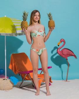 Fêmea nova alegre no roupa de banho que guarda o abacaxi no estúdio