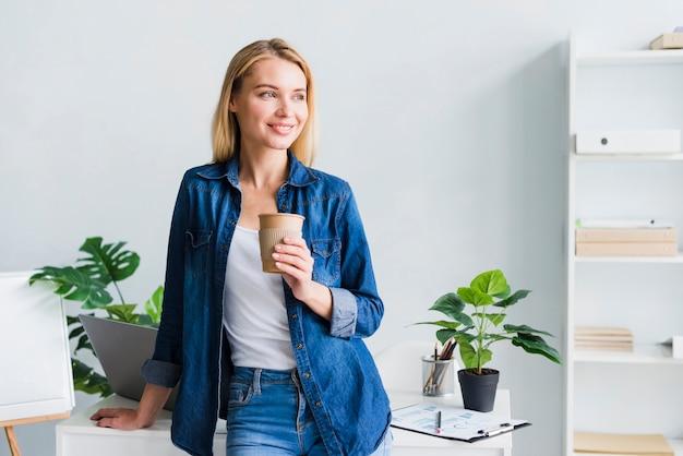 Fêmea nova alegre que guarda o copo de papel na ruptura no trabalho