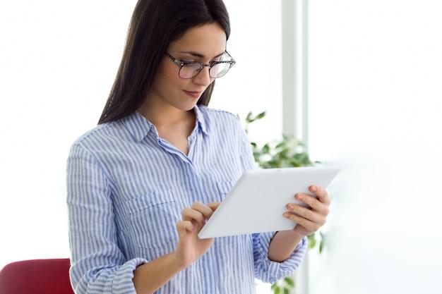 Fêmea nova nos vidros usando o laptop
