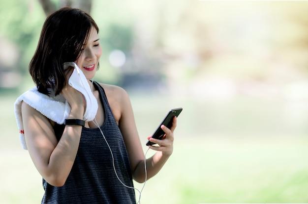 Fêmea nova que usa o telefone móvel após o exercício com felicidade ao estar ao ar livre.