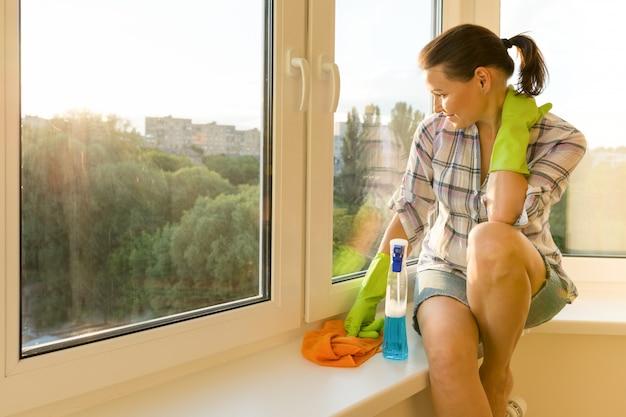 Fêmea olha para a janela limpa e lavada