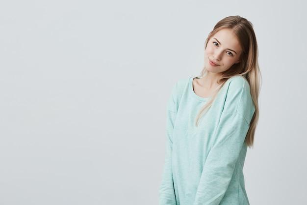 Fêmea positiva de sorriso com olhar atrativo, vestindo a parte superior azul branca frouxa, levantando contra a parede cinzenta. mulher feliz, com longos cabelos loiros, mostrando emoções positivas depois de receber um elogio agradável