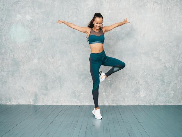 Fêmea pulando no estúdio perto da parede cinza