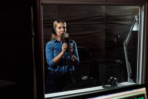 Fêmea que canta um canto com telefone celular no estúdio de gravação. você