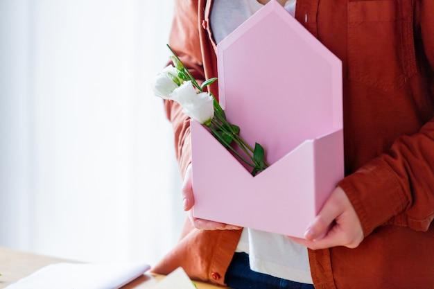 Fêmea que guarda um envelope cor-de-rosa com rosas brancas.
