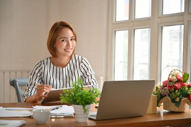 Fêmea que senta-se na tabela do escritório com papel de original de molhadela.