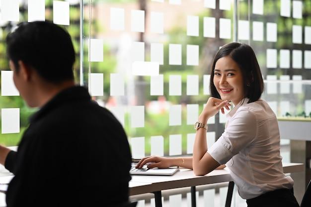 Fêmea que trabalha no portátil no espaço de funcionamento do co com o retrato disparado olhando a câmera.