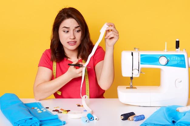 Fêmea que usa tesouras para cortar a parte de matéria têxtil isolada sobre o amarelo.