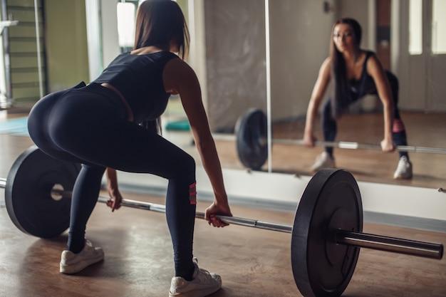 Fêmea, realizando exercícios de levantamento terra com barra de peso. jovem confiante fazendo exercícios de levantamento de peso no ginásio