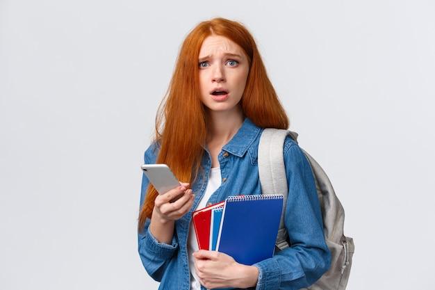 Fêmea ruiva bonita triste e inquieta e triste lendo algo preocupante no visor do telefone, segurando móveis, mochila e cadernos como na universidade
