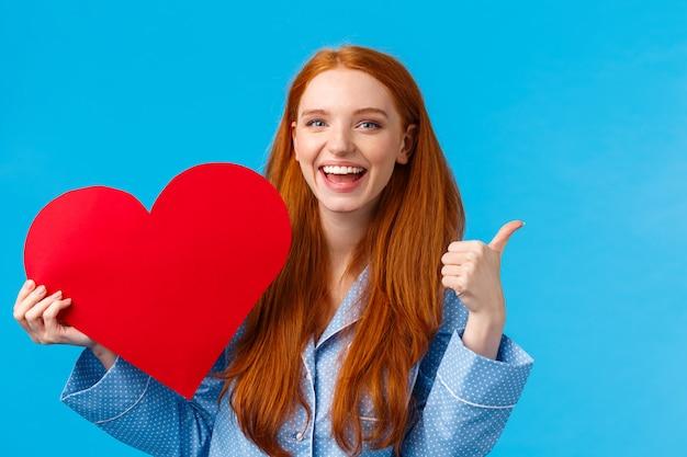 Fêmea ruiva jovem alegre positiva e animada mostrando o polegar para cima em como ou aprovação