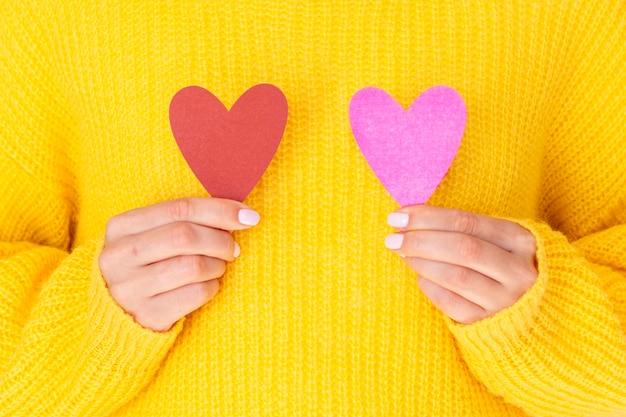 Fêmea, segurando corações de papel vista frontal