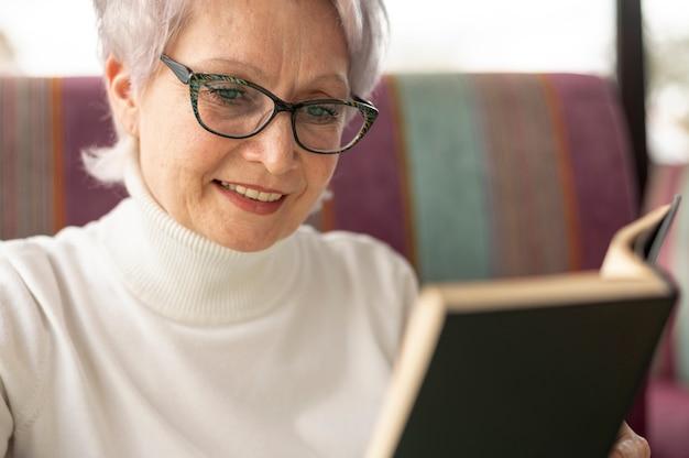 Fêmea sênior de close-up na leitura do restaurante