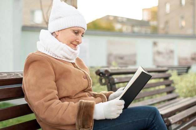 Fêmea sênior no tempo de leitura do parque