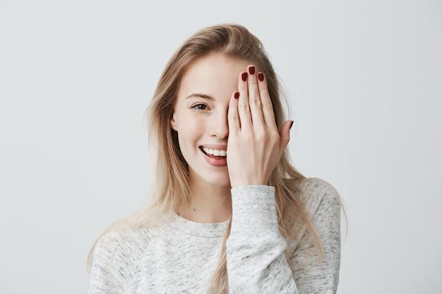 Fêmea sorridente feliz com aparência atraente e cabelo loiro, vestindo blusa solta, mostrando seu sorriso amplo, com bom humor, fechando o olho com a mão