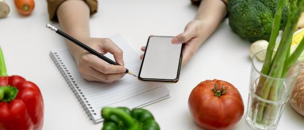 Fêmea, tomar notas de receita no caderno em branco, enquanto procurava informações no smartphone de tela em branco