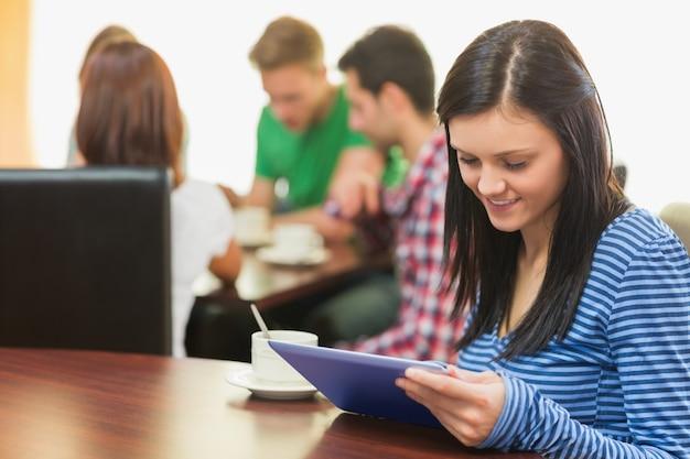 Fêmea, usando o tablet pc enquanto tomando café na cafeteria