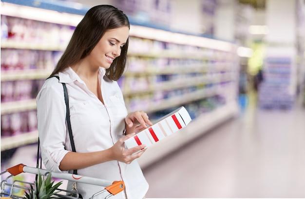 Fêmea, verificando a rotulagem dos alimentos no supermercado.