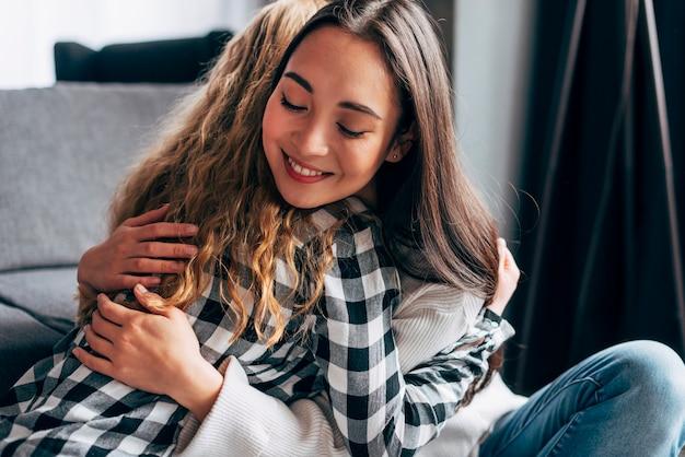 Fêmeas jovens, abraçar, enquanto, sentar chão