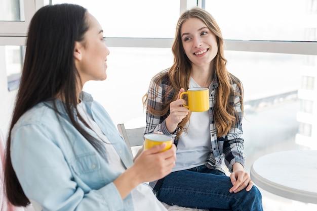Fêmeas jovens, sentando, com, canecas