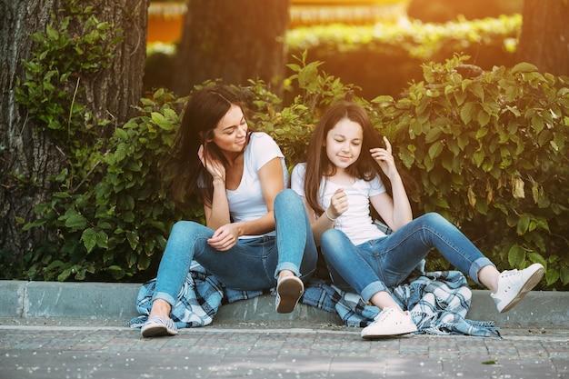 Fêmeas morenas sentadas na calçada do pavimento