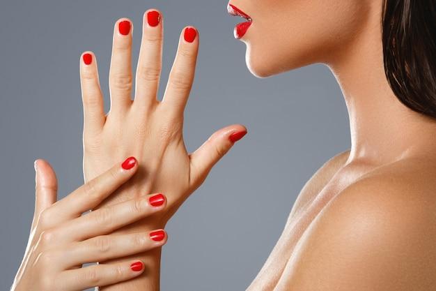 Feminina boca e unhas com manicure vermelho e batom.