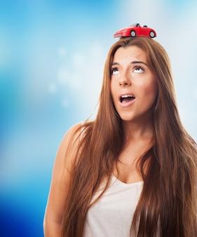 Feminina de cabelos compridos com um carro vermelho pequeno em sua cabeça