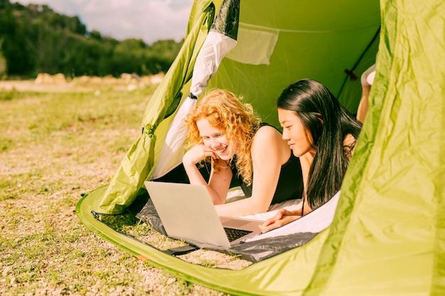 Femininas, amigos, usando computador portátil, em, barraca
