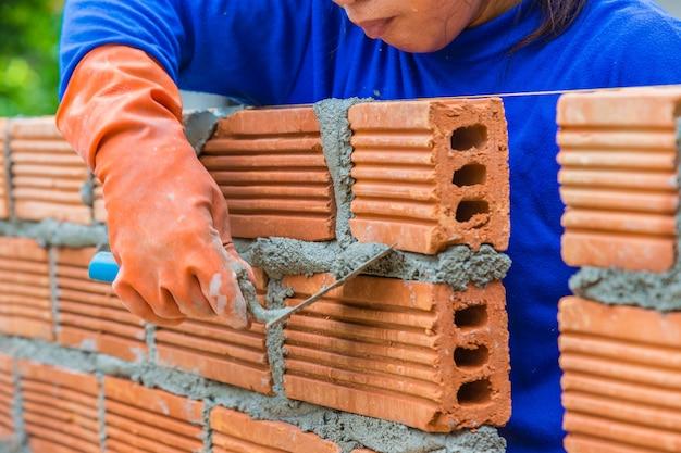 Femininas, construção, trabalhador, deitando, parede tijolo