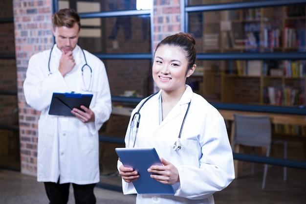 Femininas, doutor, ficar, perto, biblioteca, com, tablete digital, e, doutor masculino, estar, e, pensando