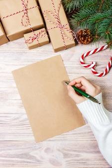 Femininas mãos escrevendo uma carta para o papai noel, presentes de natal em um de madeira, ver os de cima