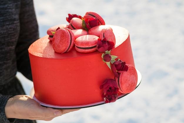 Femininas mãos segurando a placa com delicioso delicioso bolo vermelho caseiro com macarons decorados com flores sobre fundo borrado espaço luz cópia.