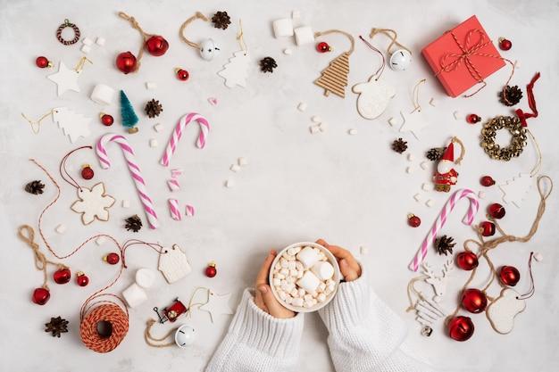 Femininas mãos segurando a xícara com chocolate quente decorado marshmallows. tema de natal