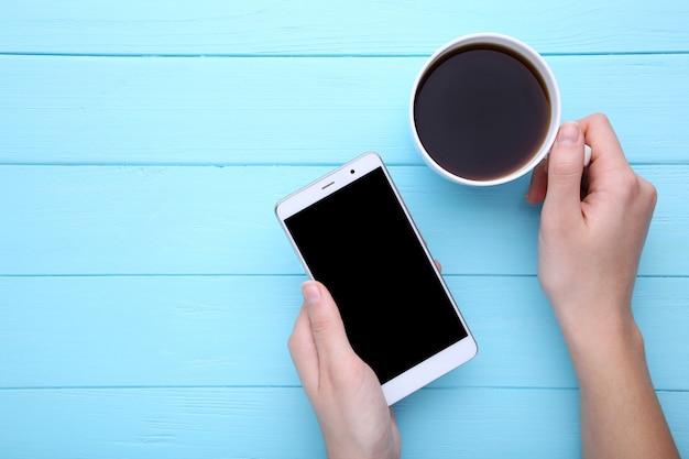 Femininas mãos segurando a xícara de café e smartphone em azul de madeira.