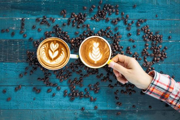 Femininas mãos segurando copos com grãos de café sobre fundo de madeira azul grunge