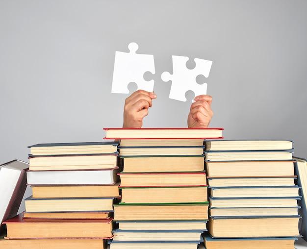 Femininas, mãos, segurando, grande, branca, puzzles, sobre, um, pilha livros