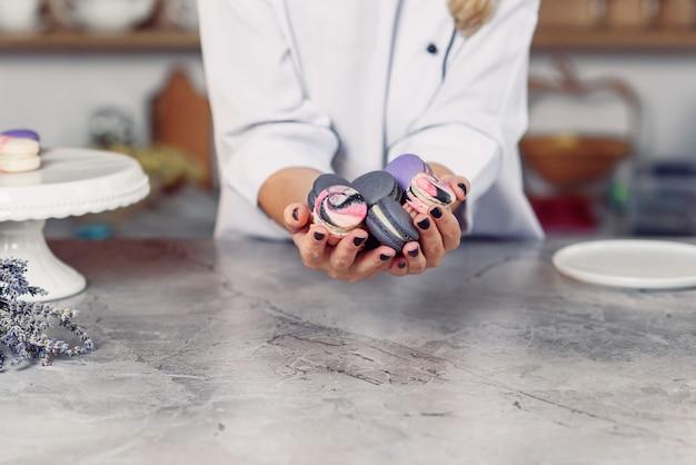 Femininas mãos segurando macaroons de francês coloridos sobre uma mesa de mármore.
