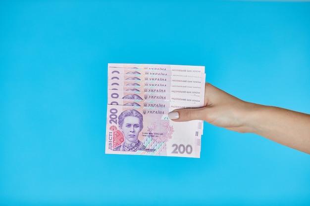 Femininas mãos segurando notas ucranianas em azul