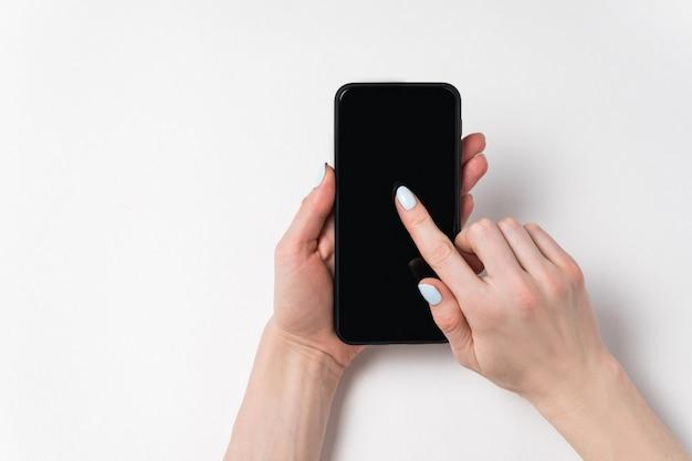 Femininas mãos segurando o telefone e mostrando na tela. tela preta, fundo branco, copie o espaço