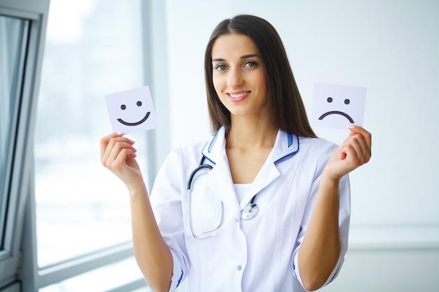 Femininas, mãos, segurando papel, com, símbolo, triste, e, alegre, sorrizo